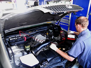 automotive technician performing mechanical service to vehicle